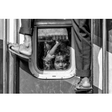 Little boy is looking outside from the window of train where a man trying to reach the train rooftop in busy hour to catch the train