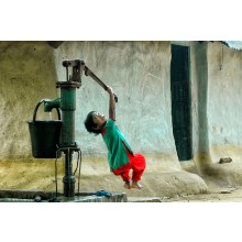 A little girl is trying to get drinking water   from a hard deep tube well , where pure water is hardly found in the hilly area