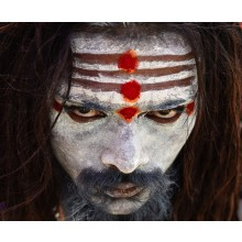 This is a photograph of an aghori who are basically the worshiper of Lord Shiva - The Destroyer.  They are people who live in close association with nature,  are smeared in ashes of cremated body and also eat the flesh of the dead. They are monists who se